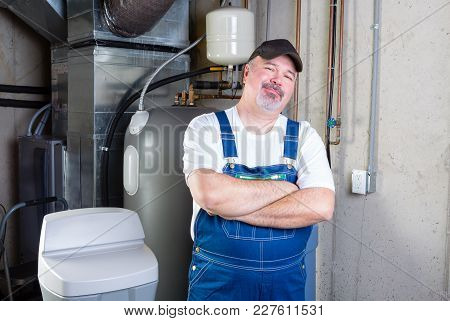 Confident Workman Or Home Installer Standing Smiling At The Camera With Folded Arms In A Basement Ut