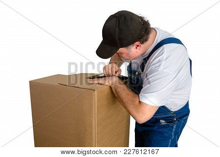 Male Worker Wearing Dungarees Opening Cardboard Box Against White Background