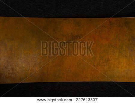 Aged Copper Plate On Black Cloth, Old Worn Metal Background, Close Up.