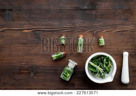 Harvest Medicinal Herbs. Greens In Mortar Bowl And Herbs In Small Bottles On Dark Wooden Background
