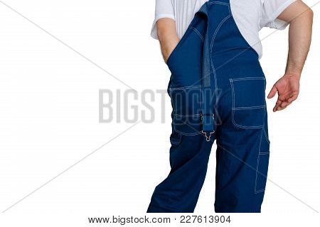 Workman In Dungarees With His Hand Inside The Back Of The Garment To Scratch Or Adjust A Discomfort