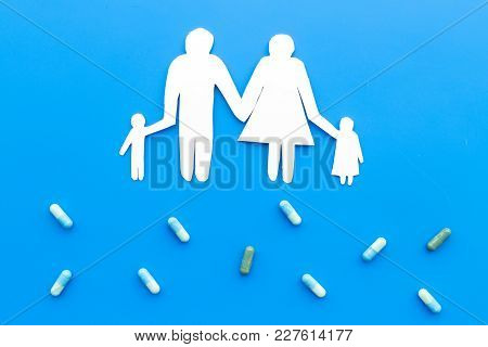 Prevention Of Diseases. Medicine For Family Health. Color Pills Near Silhouette Of Family On Blue Ba