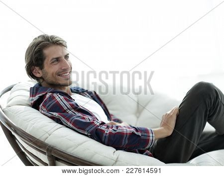 close-up. smiling guy is resting in a large comfortable chair