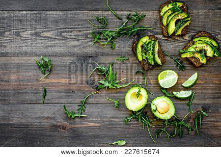 Have A Bite With Healthy Snacks. Avocado Toast On Dark Wooden Background Top View.