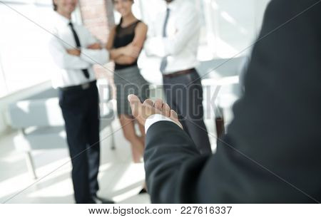 rear view.closeup. businessman holding out hand for a handshake.