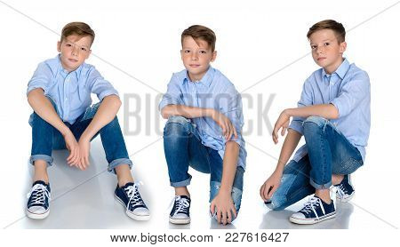A Teenager Boy Lies On The Floor In A Studio On A White Background. The Concept Of A Happy Childhood