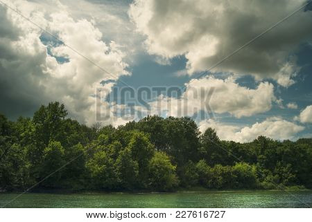 Forest Above The River Under The Summer Cloudy Sky.