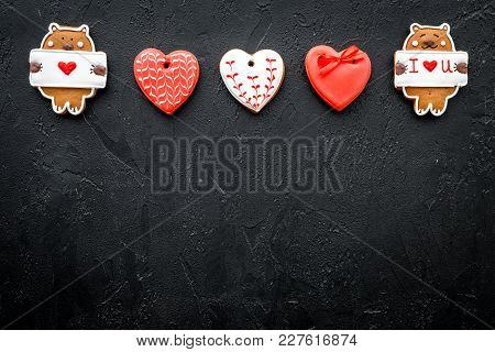 Sweet Gift For St Valentine's Day. Heart Shaped Gingerbread On Black Background Top View Copy Space