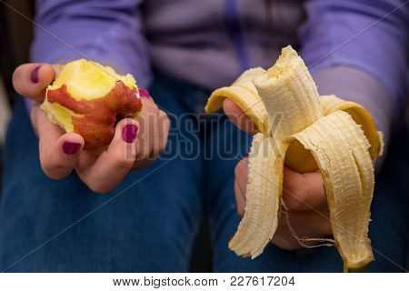 Someone Holding A Bitten Apple And A Bitten Banana In Their Hands