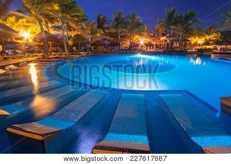 PLAYA DEL CARMEN, MEXICO - JULY 11, 2011: Swimming pool at the resort of RIU Yucatan Hotel in Playa del Carmen, Mexico. RIU Hotels & Resorts has more than 100 hotels in 19 countries.