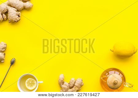 Warming Tea With Lemon And Ginger. Cup, Teapot, Ginger Root On Yellow Background Top View.