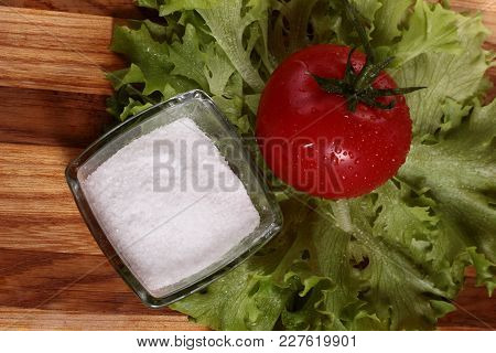 Still Life With Tomato Salad Leaves And Salt Shaker