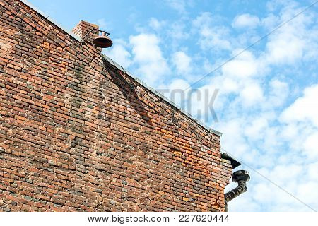 House Brick Wall Gable With Weathered Drainpipe On Corner And Lantern On Chimney Against Blue Cloudy