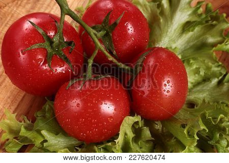 Red Juicy Tomatoes With Lettuce Leaves On The Table