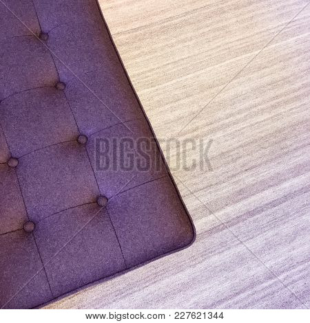 Close-up Of A Purple Ottoman On A Striped Carpet. Modern Furniture.