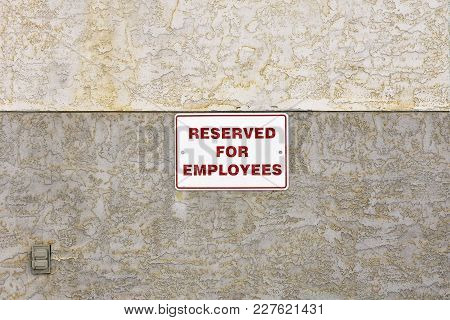 An Image Of A Red And White Reserved Parking Sign On A Brown Stucco Wall.