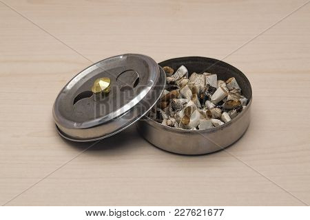 Ashtray With Lid And Cigarette Butts Against The Background Of A Light Table