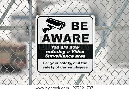 An Image Of A Video Surveillance Sign On A Chain Link Fence.