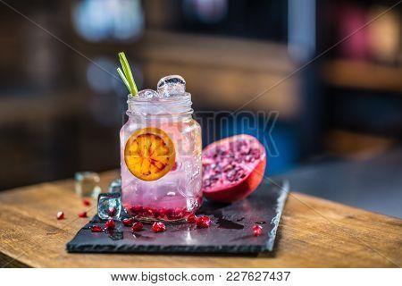 Lemonade. Lemonade Vith Fresh Fruit Pomegranate On Barcounter In Pub Or Restaurant