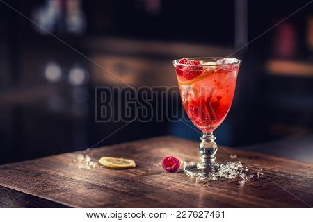 Alcoholic Beverage With Raspberries Lemon And Ice On Bar Counter In Pub Or Restaurant