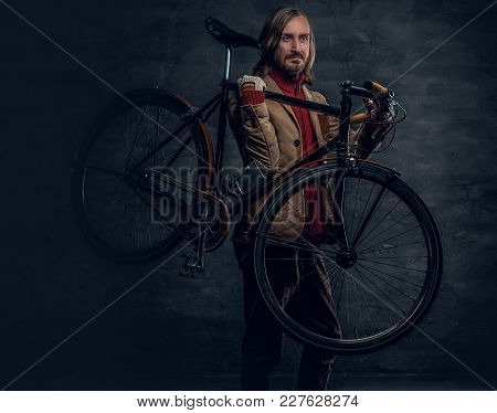 Stylish Bearded Male With Long Hair Holds Fixed Bicycle On A Shoulder In A Studio.