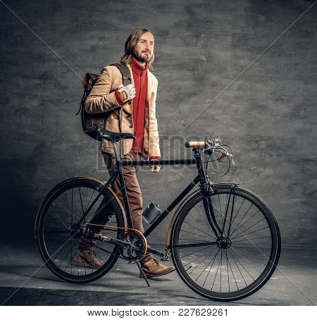 Casual Bearded Hipster Male Posing With Single Speed Bicycle Over Grey Background.