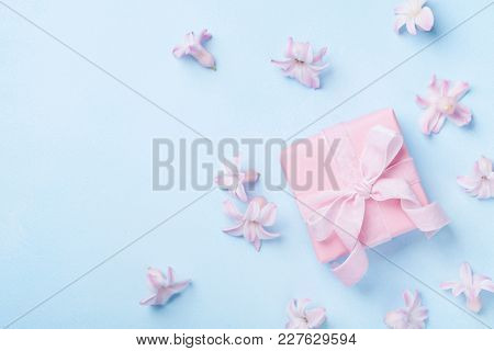 Pink Flowers And Present Or Gift Box On Blue Pastel Table Top View. Greeting Card For 8 March, Woman