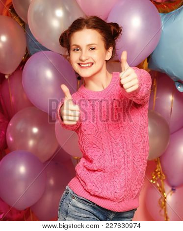 lifestyle and people concept: Portrait of happy smiling young woman showing okay gesture, over   background of balloons.