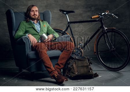 Casual Male With Long Blond Hair Dressed In A Green Jacket Sits On A Chair With Single Speed Bicycle