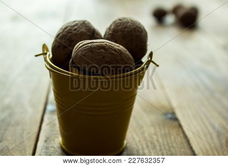 A Nuts In A Small Yellow Bucket On A Wooden Background