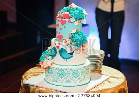 wedding cake with three tiers of white blue glaze decorated with flowers and hearts on the table poster