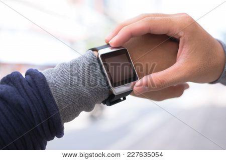 A Man Using His Smart Watch App Outdoors.