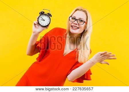 Portrait Of Attractive Smiling Blonde Woman In Glasses And Red Dress Isolated On Yellow Background W