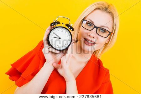Portrait Of Attractive Sexy Blonde Woman In Glasses And Red Dress Isolated On Yellow Background Hold