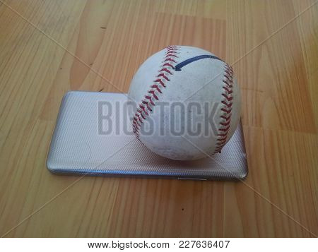 Closeup And Top View Of A White Cricket Hard Ball Over Smart Phone On Wooden Floor. Modern Playing T