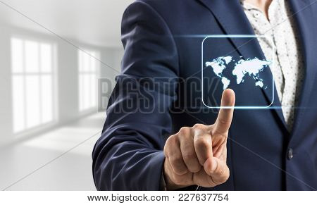Businessman Touches Glowing World Map In Bright White Office. Elements Of This Image Furnished By Na