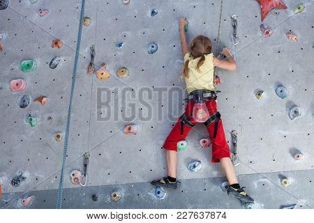 Little Girl Climbing A Rock Wall Indoor.