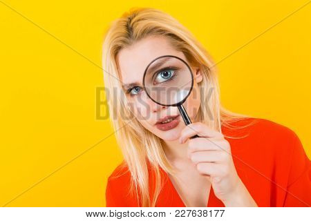Portrait Of Attractive Blonde Woman In Red Dress Isolated On Yellow Background Looking Through Magni