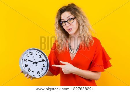 Portrait Of Curly-haired Woman In Red Dress And Eyeglasses Isolated On Orange Background Holding Clo