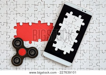 A Modern Big Smartphone With A Touch Screen And A Spinner Lie On A White Jigsaw Puzzle In An Assembl
