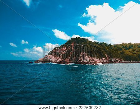 Small Island With Green Foliage In A Calm Turqoise Ocean And A Lit Sky With Some Clouds