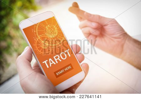 Smartphone with modern fortunetelling application on screen and hand with crossed fingers sign as a concept of psychic advisor or newest ways of divination and luck