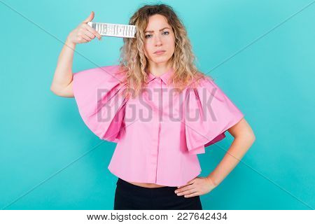 Portrait Of Attractive Bored Curly-haired Woman In Pink Blouse Isolated On Blue Backgroung Holding R