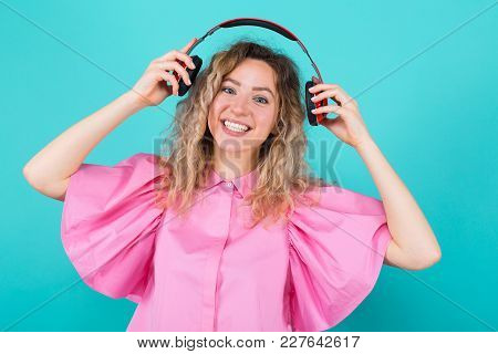 Portrait Of Attractive Smiling Curly-haired Woman Dj In Pink Shirt Isolated On Blue Background Putti