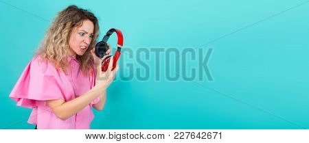 Portrait Of Attractive Dissatisfied Curly-haired Woman In Pink Shirt Isolated On Blue Background Hol