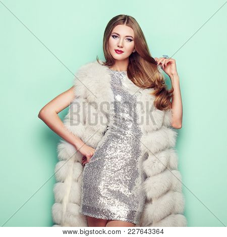 Fashion Portrait Young Woman In White Fur Coat. Girl With Elegant Hairstyle Posing On A Colored Back