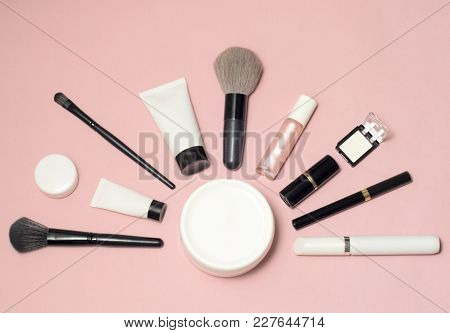 Set Of Makeup Cosmetics, Concealer, Brushes And Other Essentials On Pink Background
