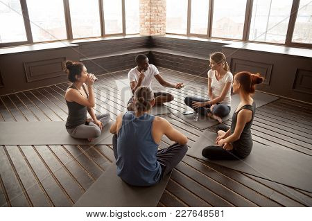 African American Yoga Instructor Talking To Diverse Group Sitting On Mat In Studio, Multiracial Happ