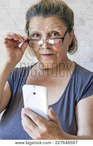An Elderly Lady With A Mobile Phone In Her Hand Looks At The Camera Through Glasses