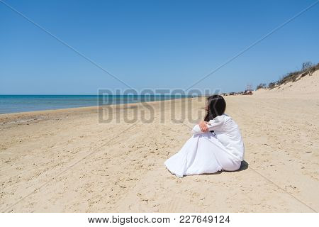 Young Woman Looking Away While Sitting At Sea Shore Side View
